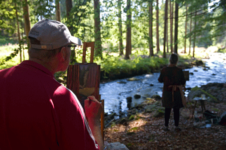 man and lady painting next to a river in woodland en plein air