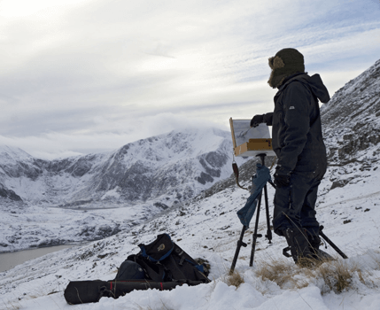 David 'DJ' Johnson painting near snowy mountains and a lake - Y Garn