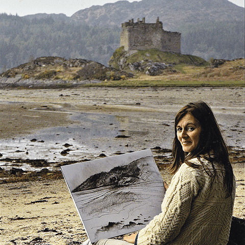 Fiona McIntyre sitting on beach drawing a castle scene