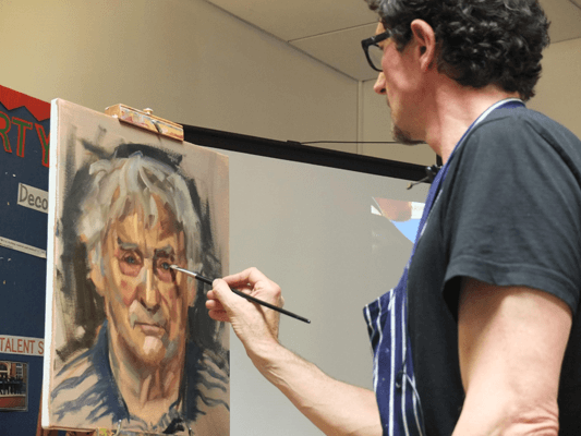 Mark Fennel painting a portrait of a man