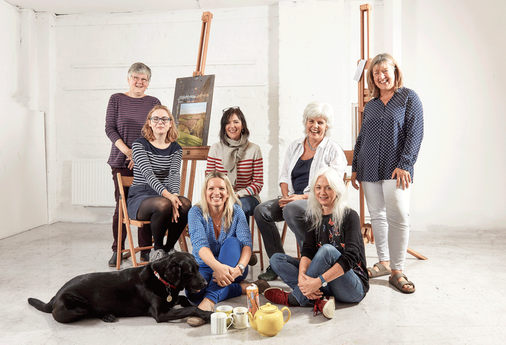 The Pegasus Art team sat and stood around easels and teaware with Digby the dog