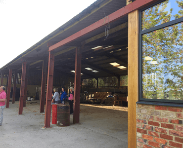 Woodchester Valley Vineyard Barn - open fronted barn with people painting inside