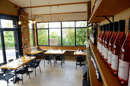 Woodchester Valley Vineyard Wine Tasting Room - tables and chair in room with wine bottles